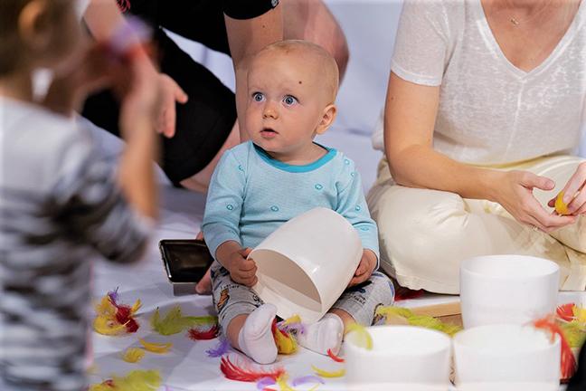 Klein Kindje leegt bakje met veertjes
