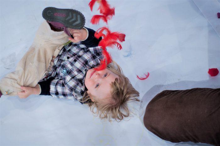 Kind speelt tijdens kindervoorstelling met rode veertjes