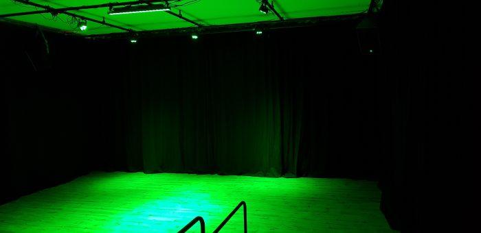 Vooraanzicht zaal kindertheater Black Cat Theatre met groene verlichting