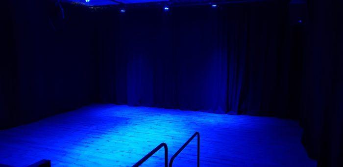Vooraanzicht zaal kindertheater Black Cat Theatre met blauwe verlichting