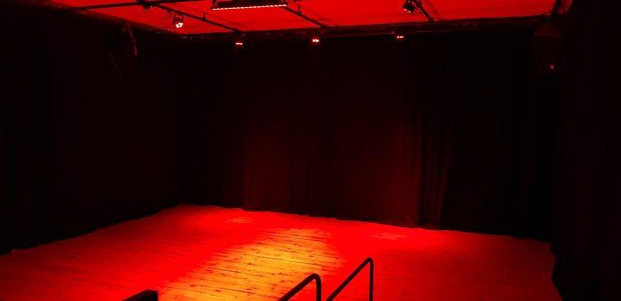 Vooraanzicht zaal kindertheater Black Cat Theatre met rode verlichting