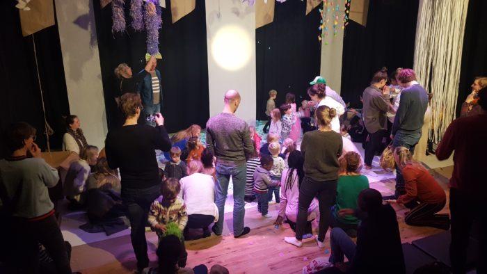 Publiek op podium in kindervoorstelling Vlindertuin
